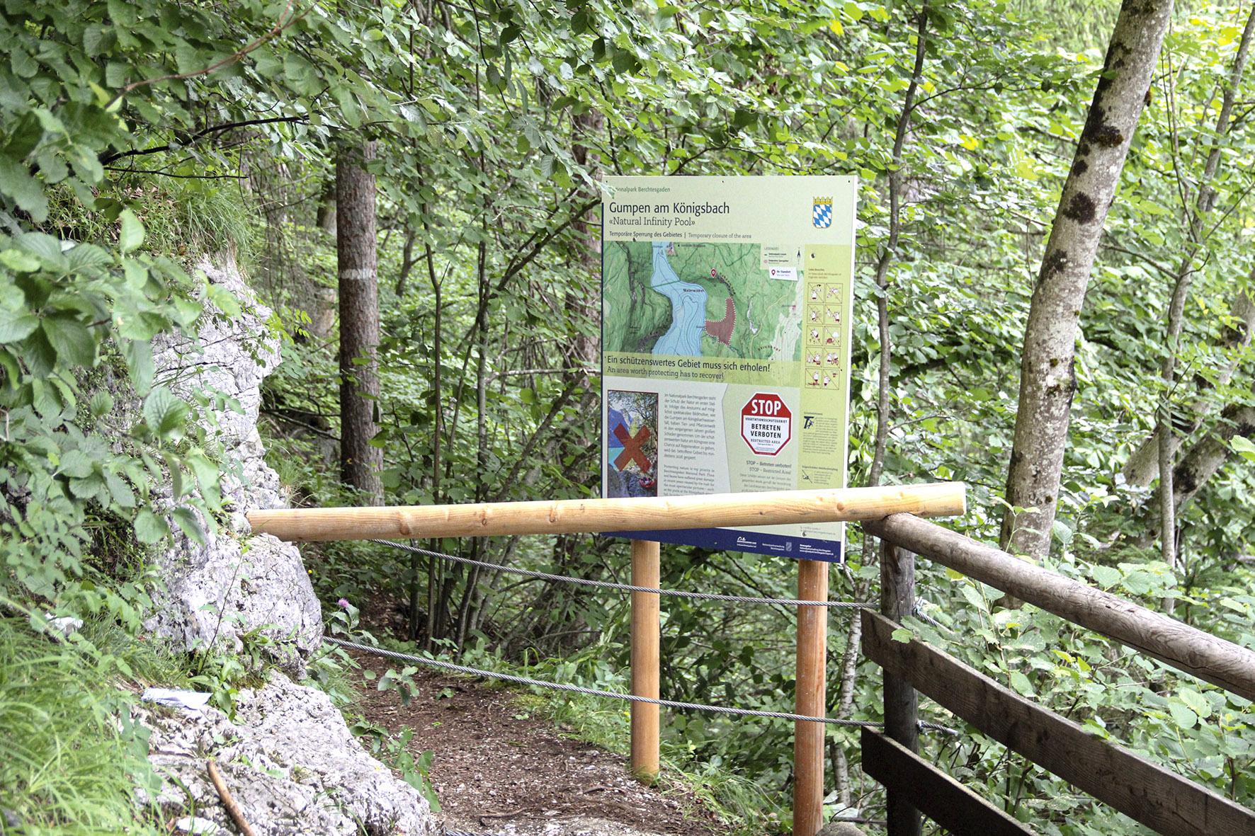Pressebild: Nationalpark-Mitarbeiter bringen die Beschilderung zur Sperrung des Vegetationsschutzgebiets im Gel��nde an.
